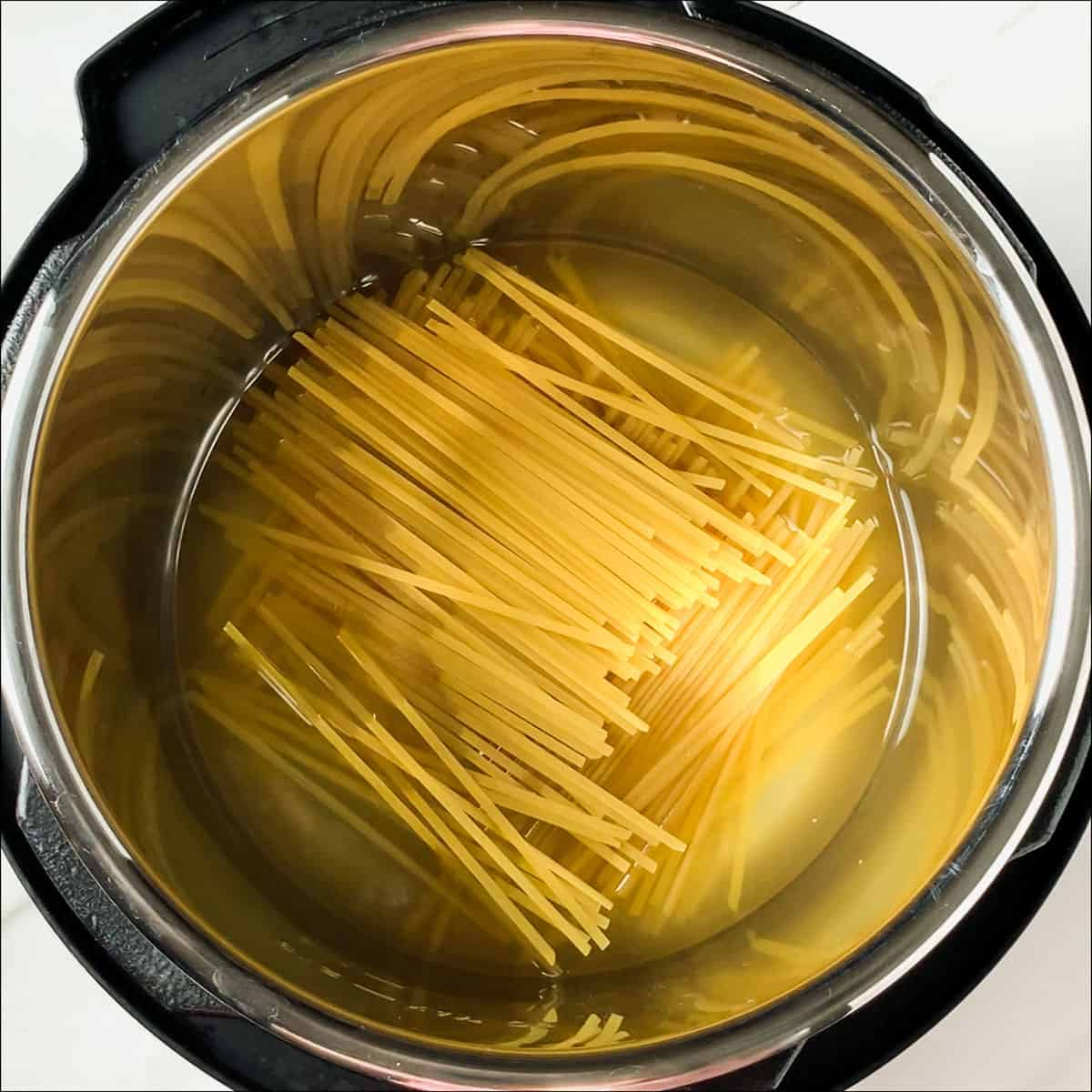 chicken broth and linguine noodles layered in the instant pot