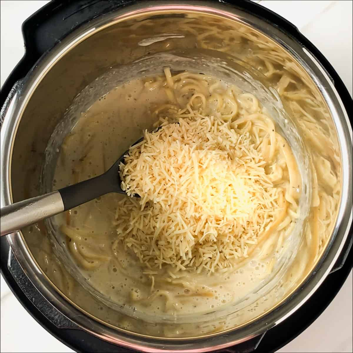 adding evaporated milk and parmesan cheese to alfredo sauce