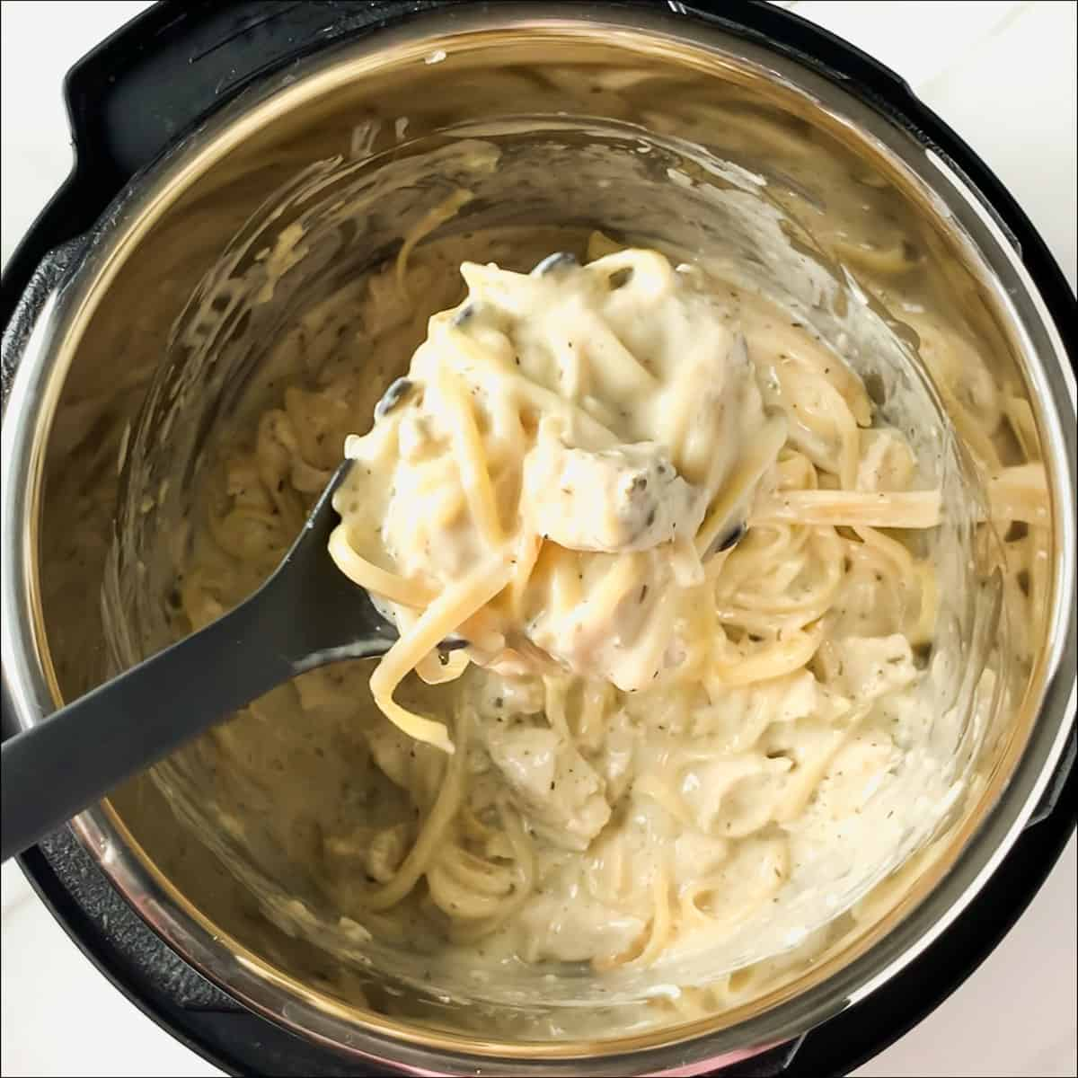 scooping out a spoonful of chicken alfredo from the instant pot