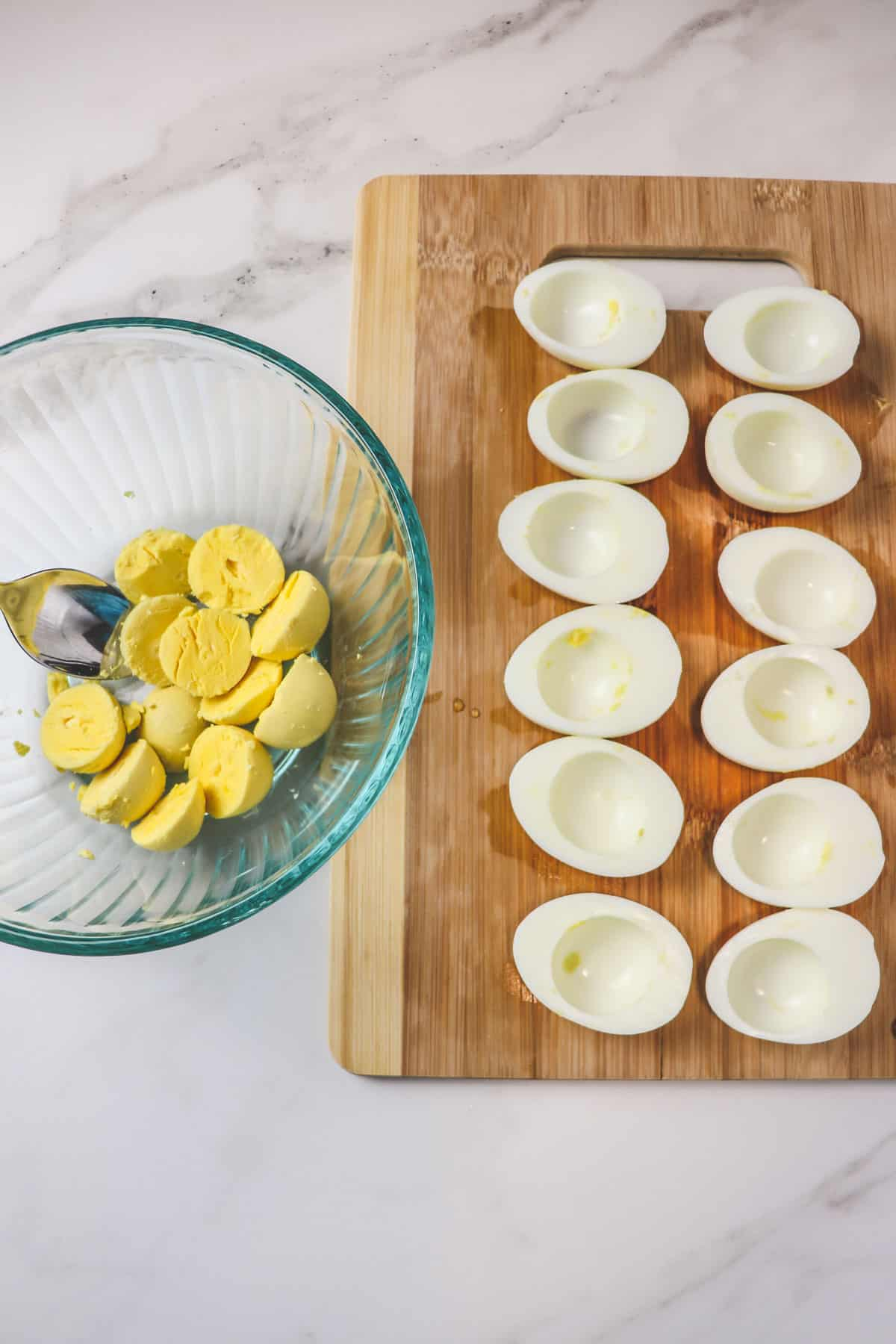 scooping cooked egg yolks out of egg whites