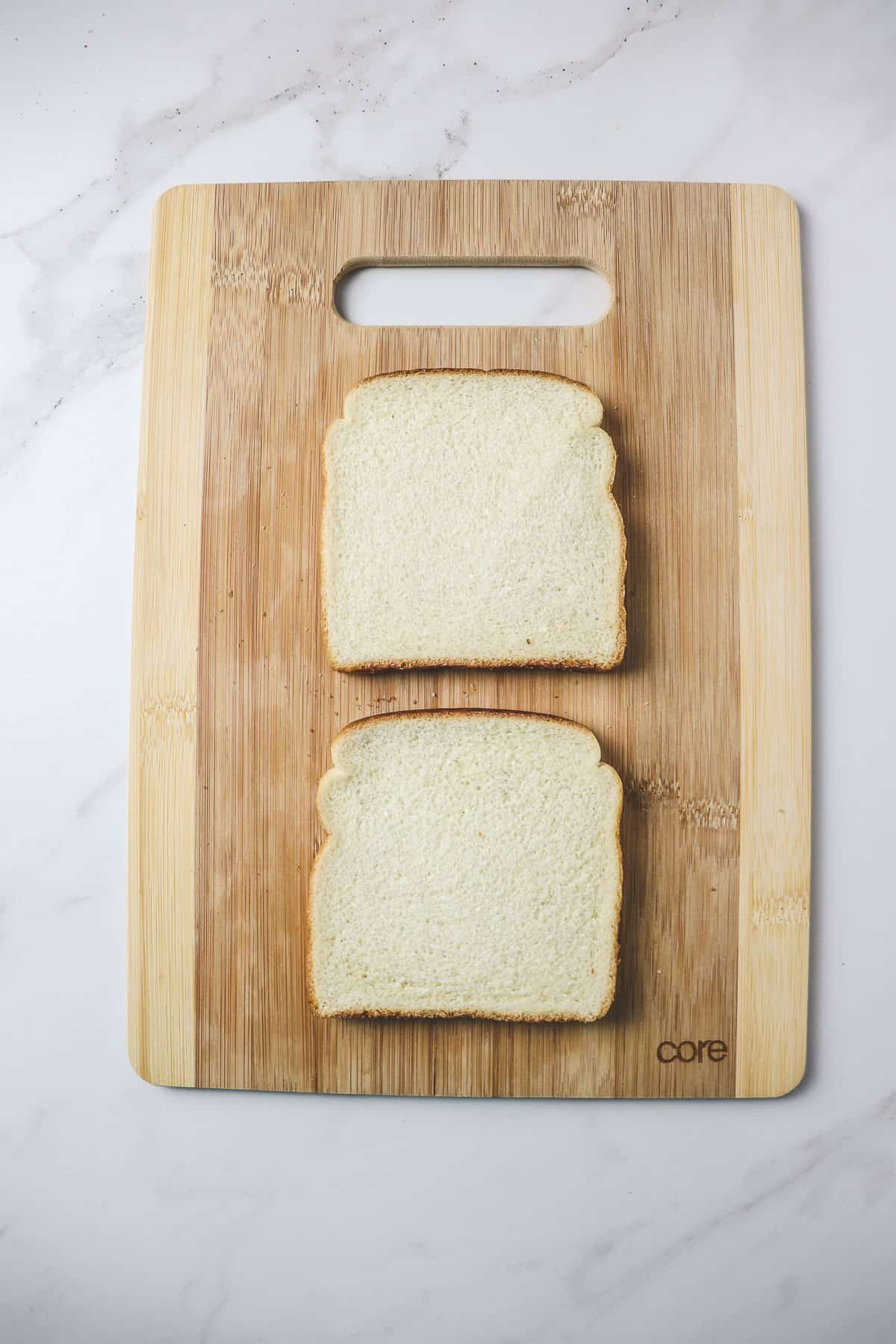 two pieces of white sandwich bread sitting on a wood cutting board