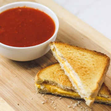 air fryer grilled cheese cut in half with a bowl of tomato soup
