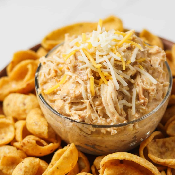 crock pot mexican chicken with shredded cheese on top sitting on plate of corn chips