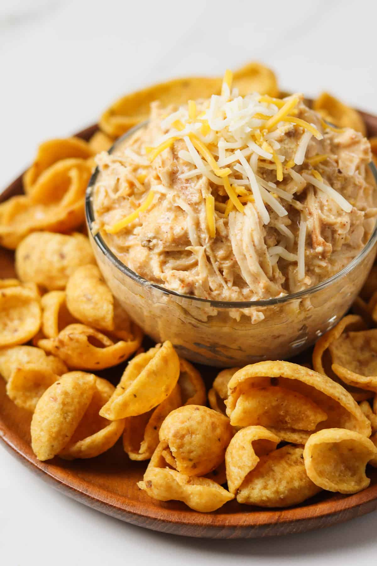 crock pot mexican chicken in glass bowl on plate with corn chips
