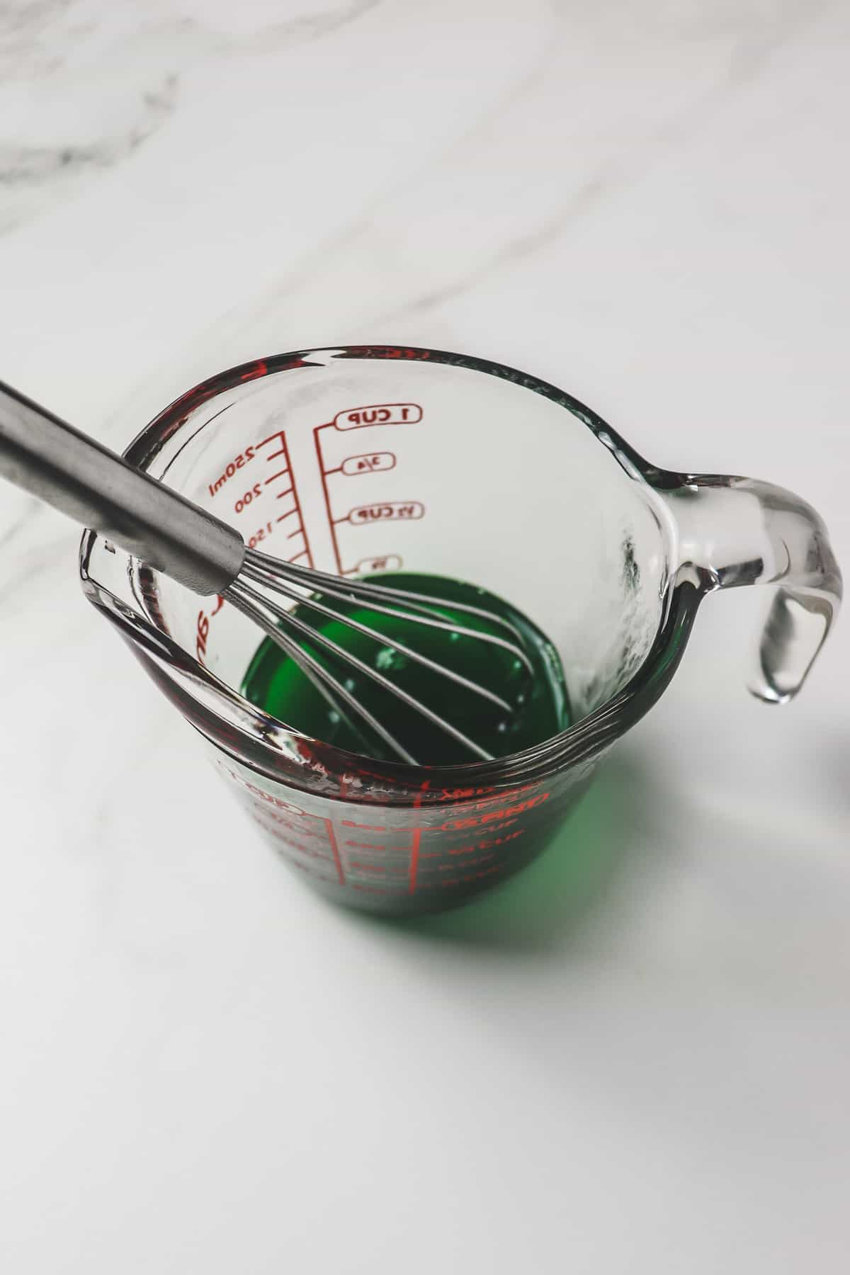 whisking the lime jello powder into boiling water in a small measuring cup
