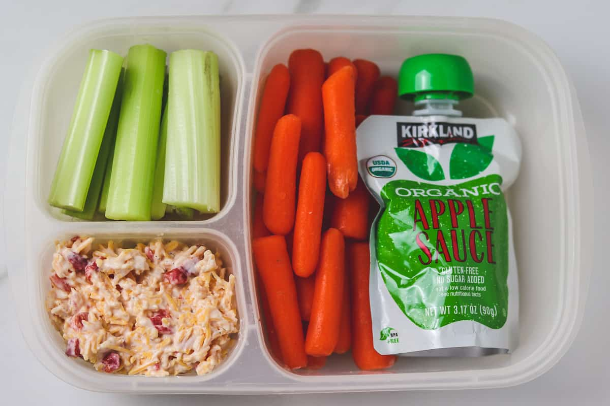 pimento cheese, carrots, celery, and apple sauce in a divided lunch container