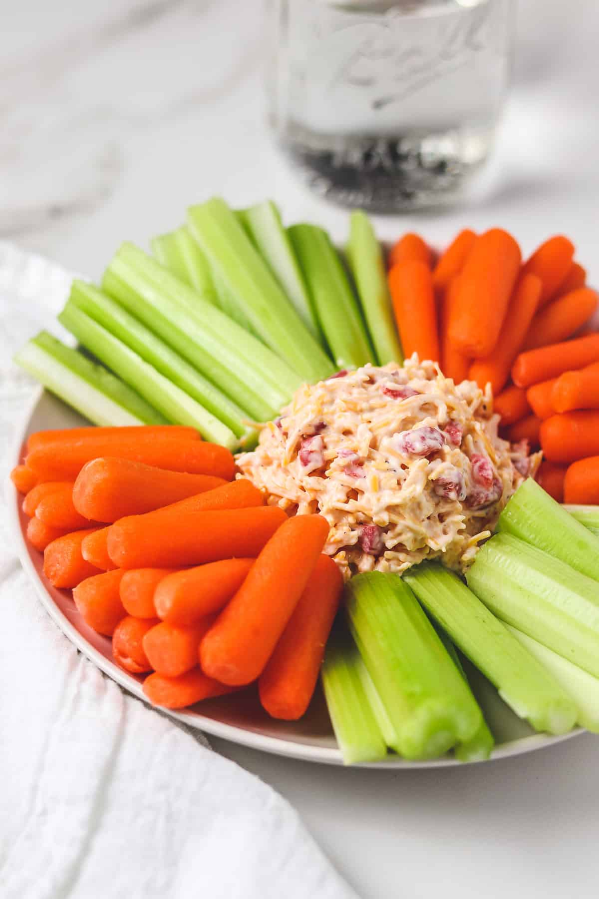 pimento cheese on a plate with carrots and celery with white napkin and water in mason jar