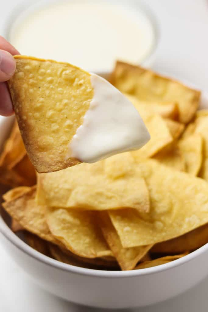 dipping a tortilla chip in queso
