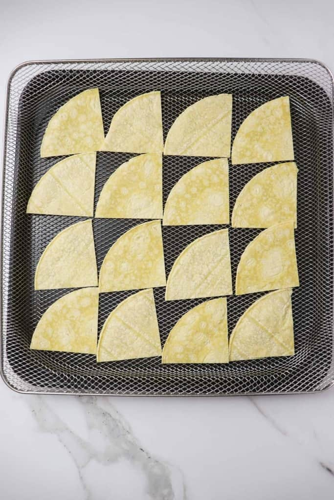 uncooked tortilla chips loaded into air fryer basket