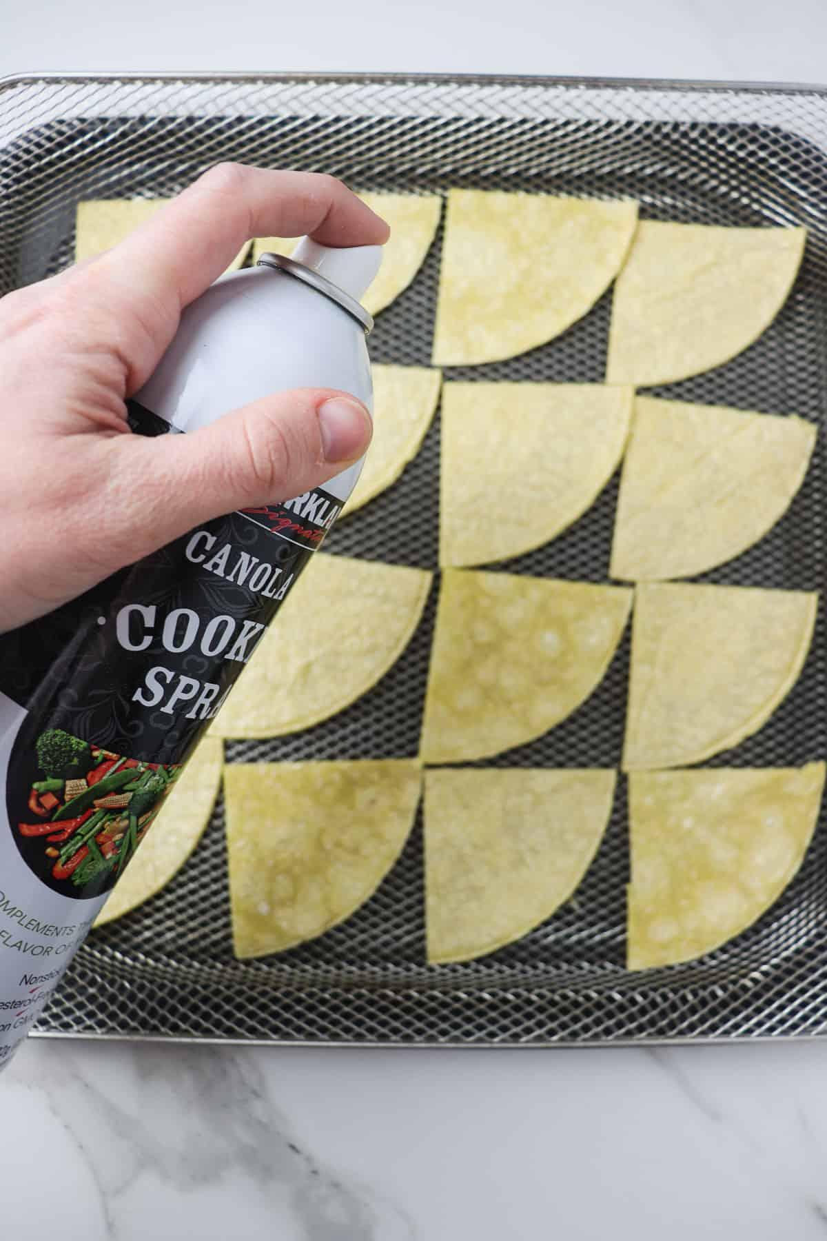 spraying corn tortillas with canola oil in air fryer basket