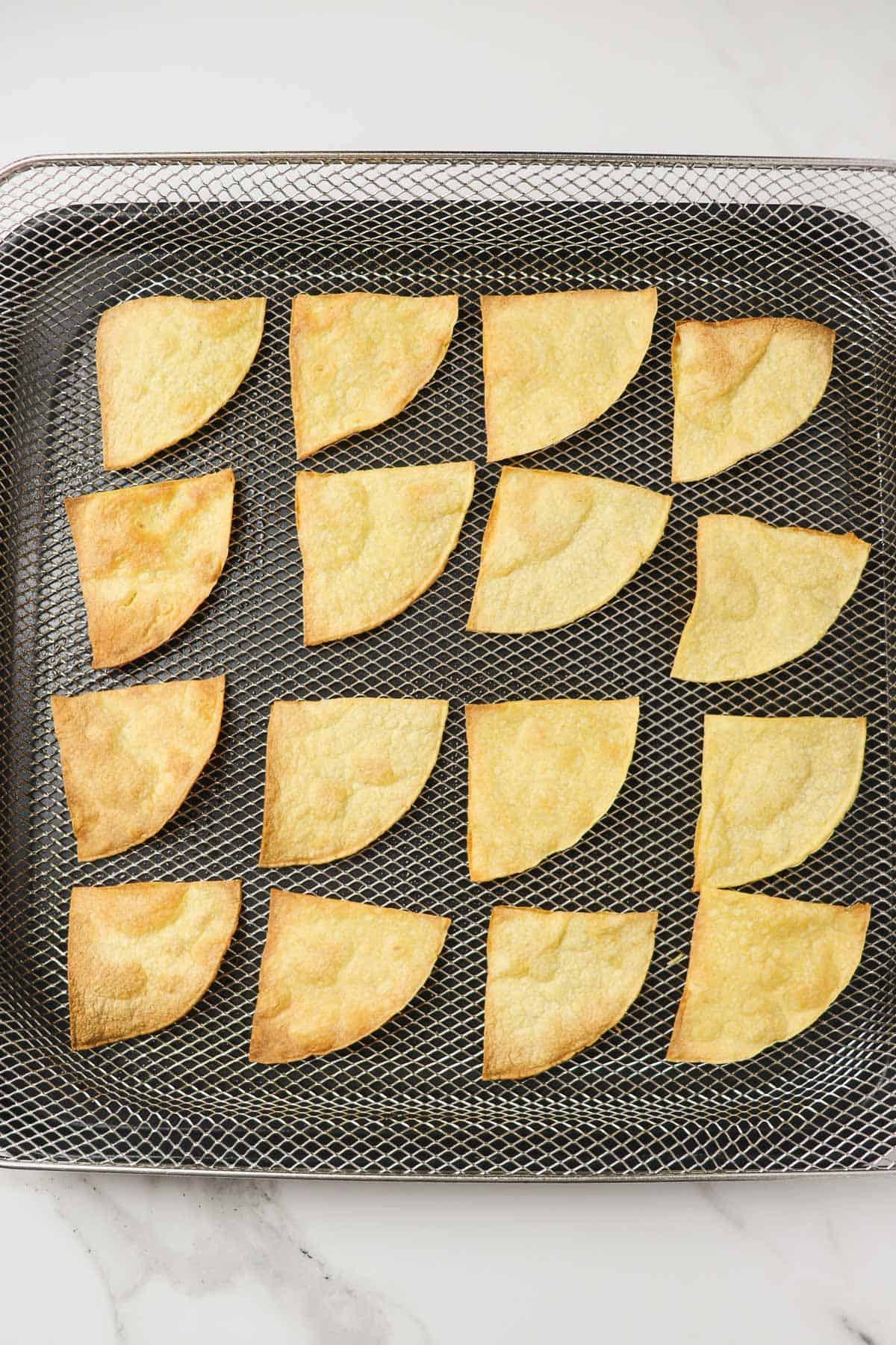 Finished air fryer tortilla chips made with corn tortillas in air fryer basket