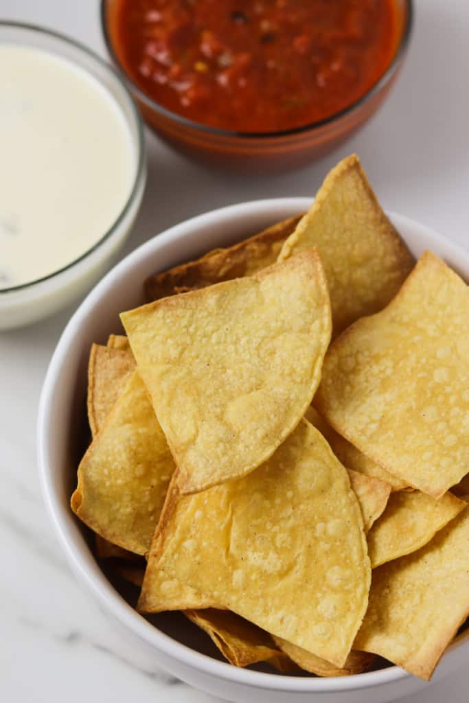 air fryer corn tortilla chips in a bowl with queso and salsa
