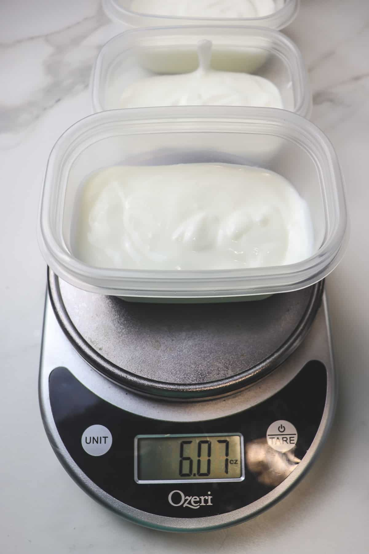 measuring yogurt portions into small plastic containers