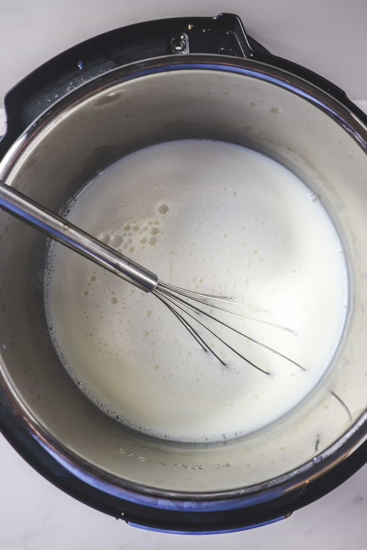 whisking the yogurt starter into the milk in the instant pot
