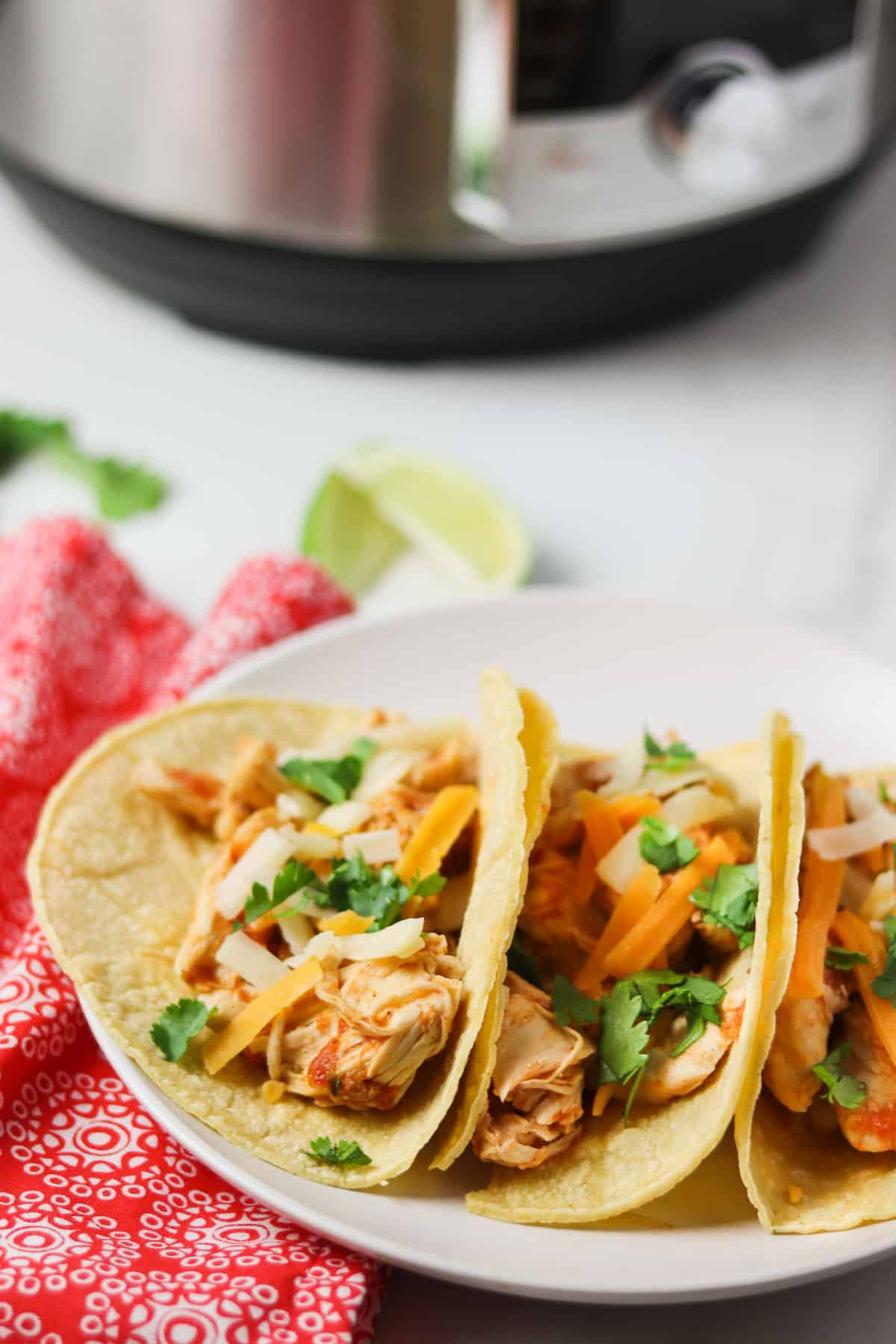 shredded chicken tacos on white plate with instant pot in the background