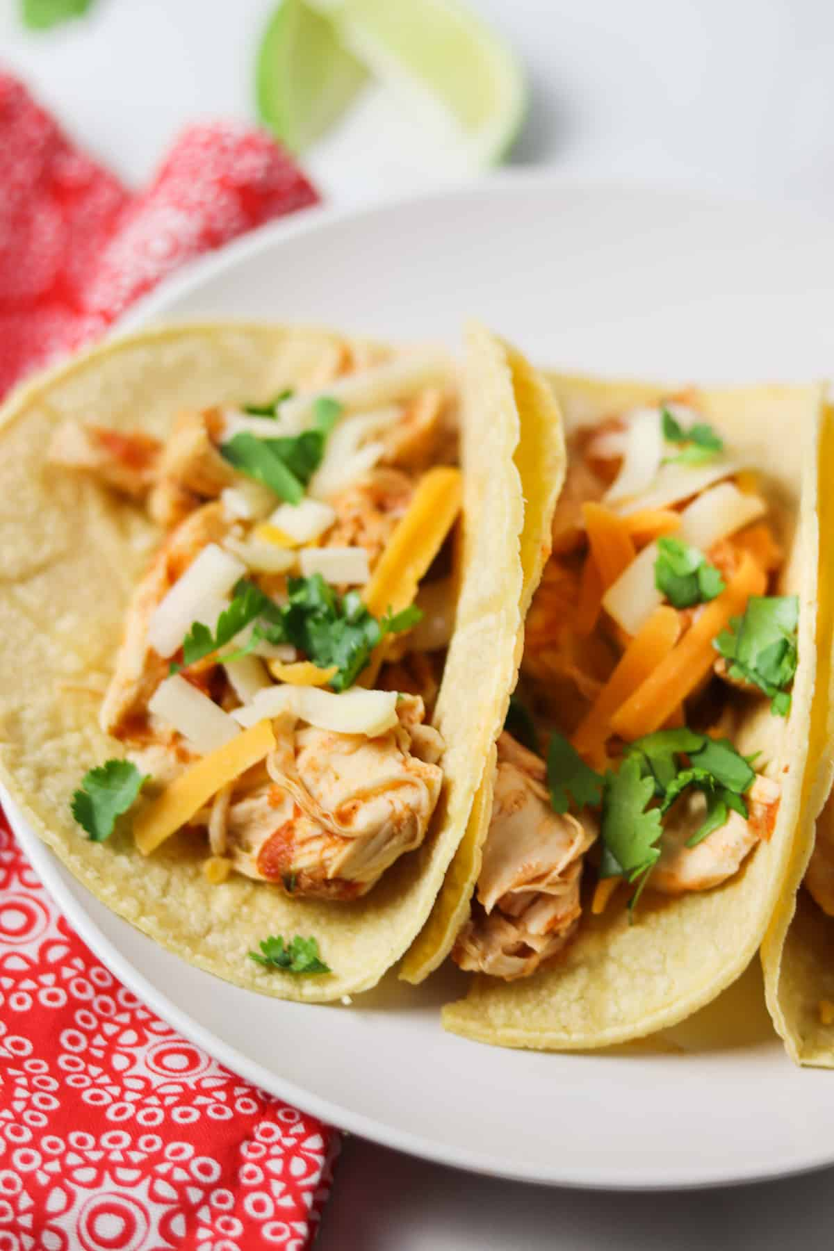 instant pot shredded chicken tacos on white plate with red napkin and limes