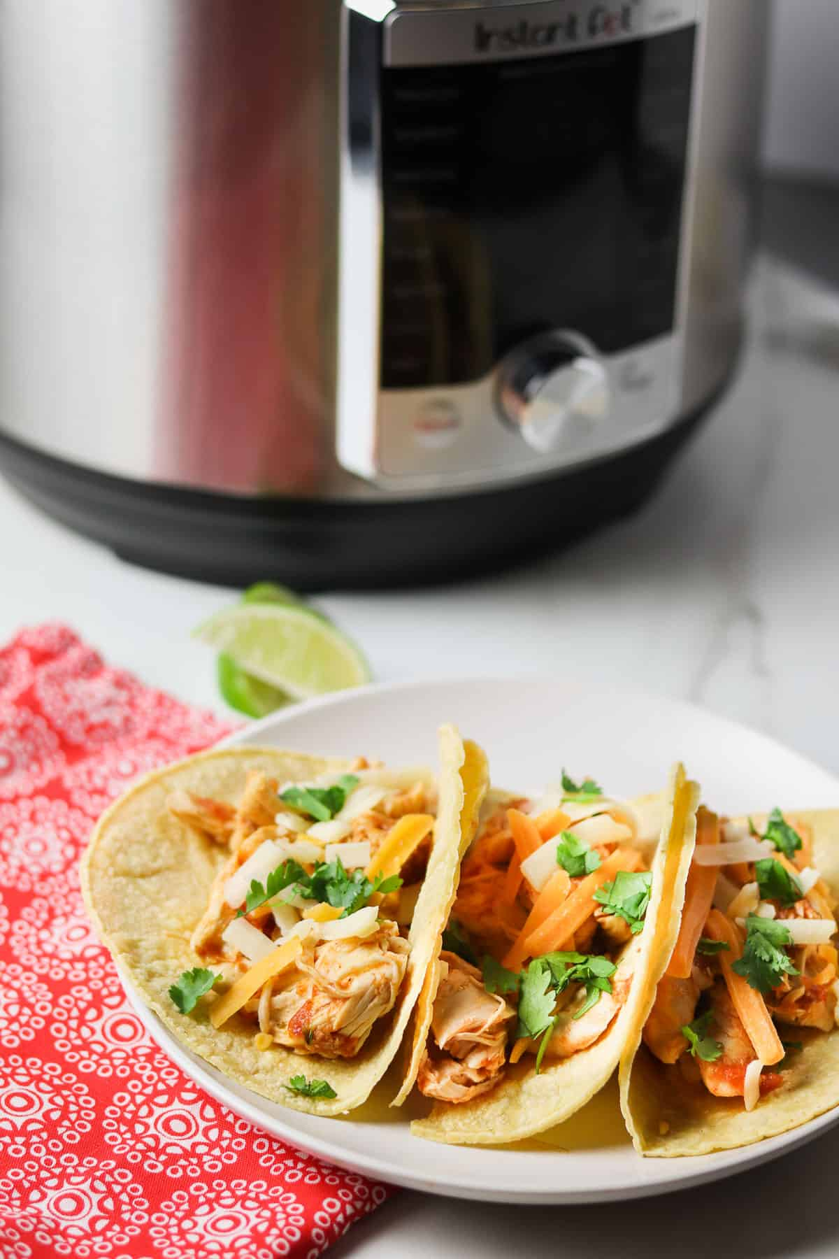 shredded chicken tacos on white plate with instant pot in background