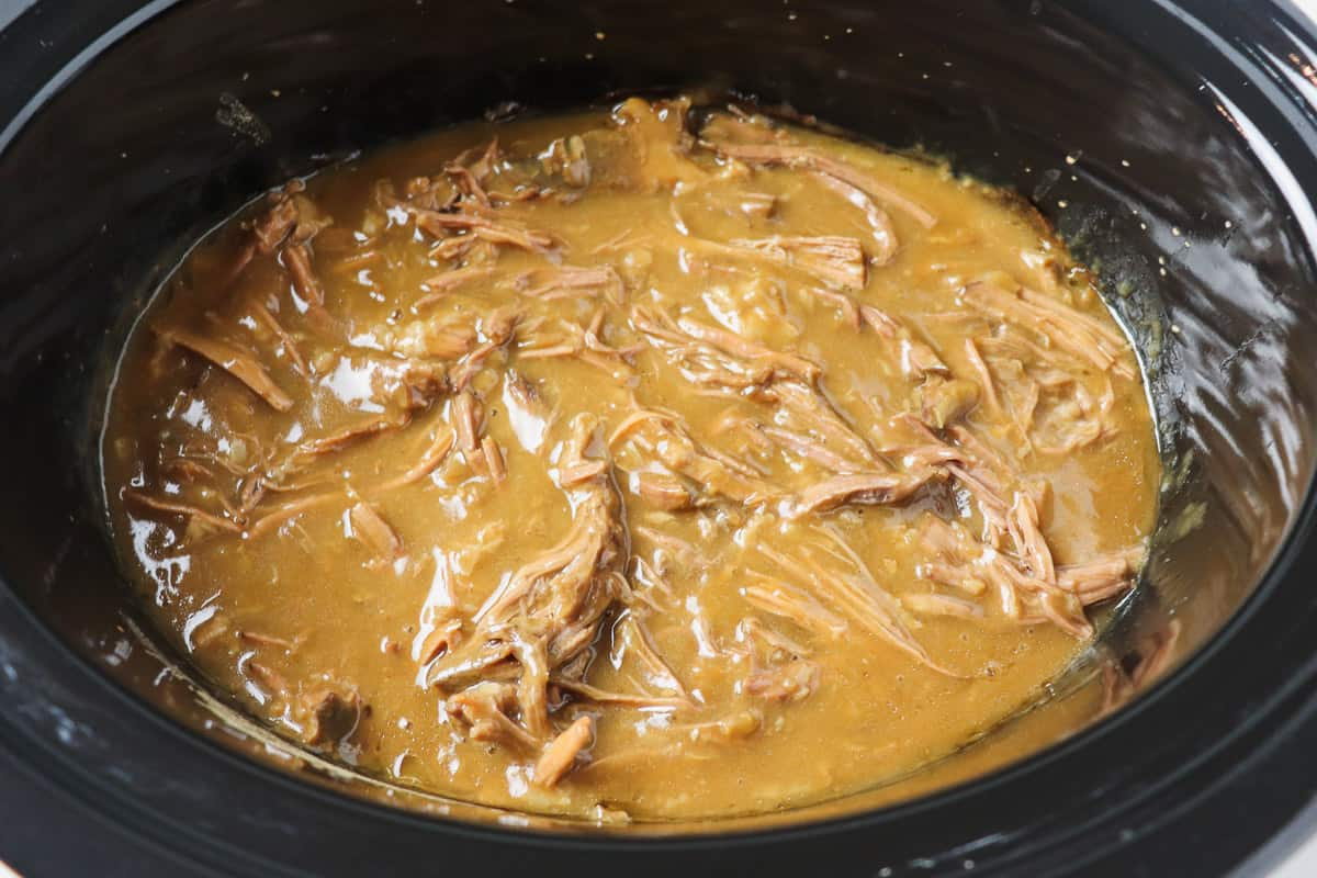 shredded pot roast with gravy inside crock pot