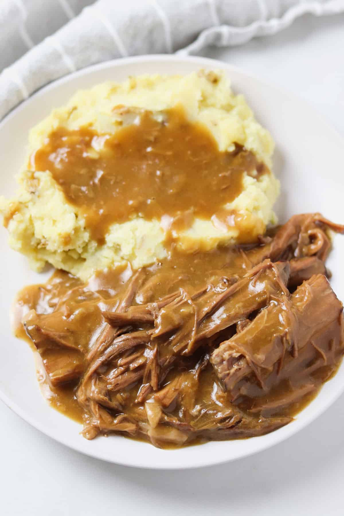 plate with pot roast with gravy and mashed potatoes with gravy