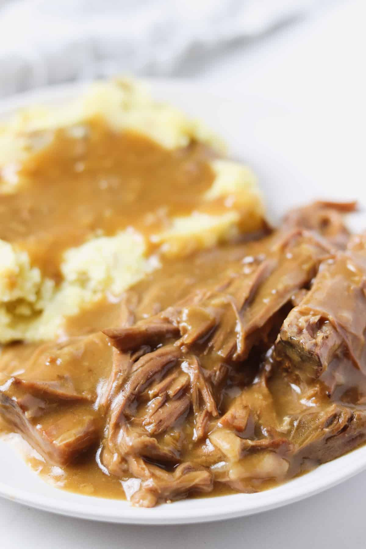 white plate with pot roast and mashed potatoes with gravy