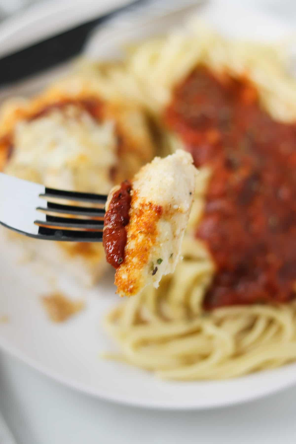 taking a bite of chicken parmesan with a fork