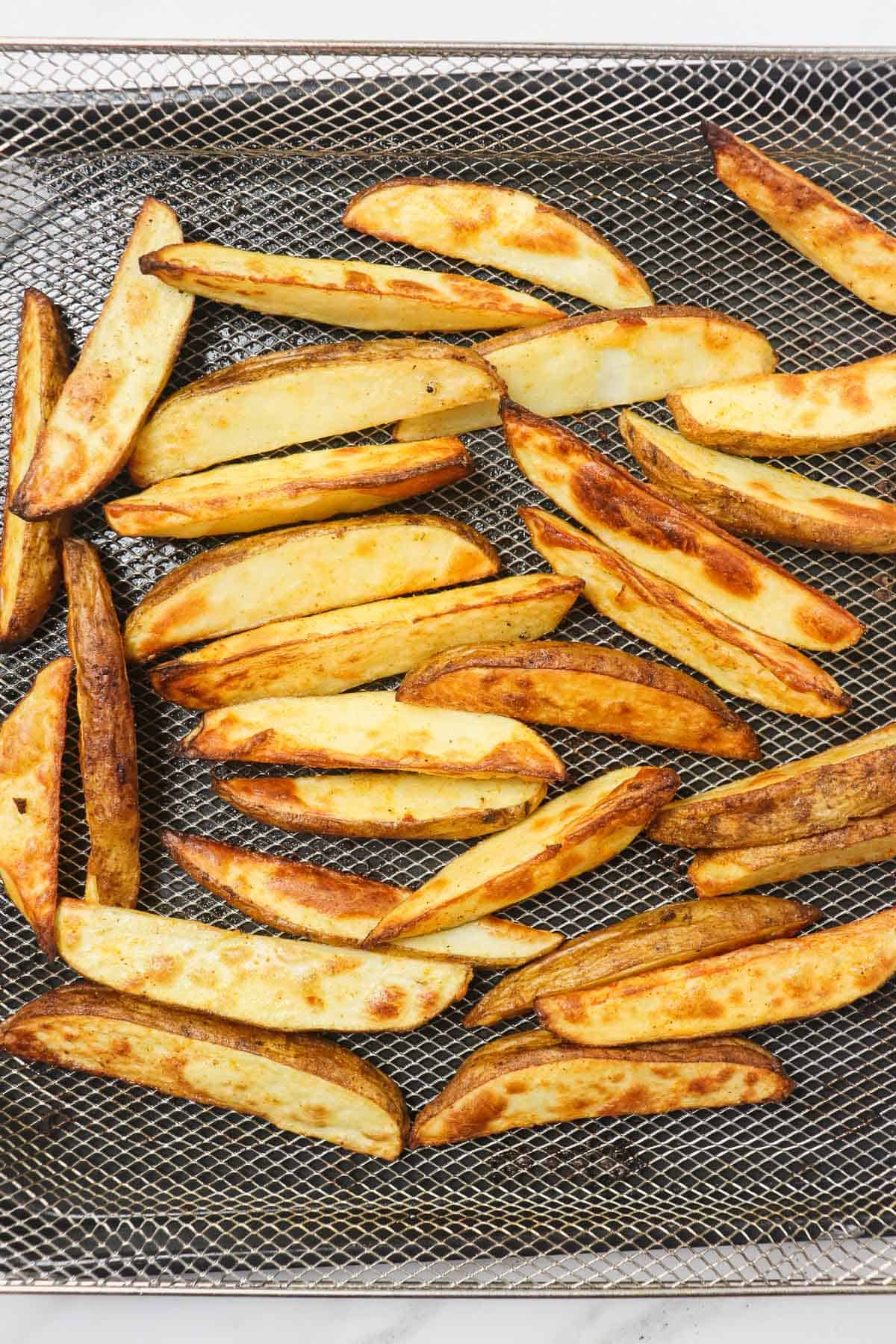 cooked potato wedges in air fryer basket