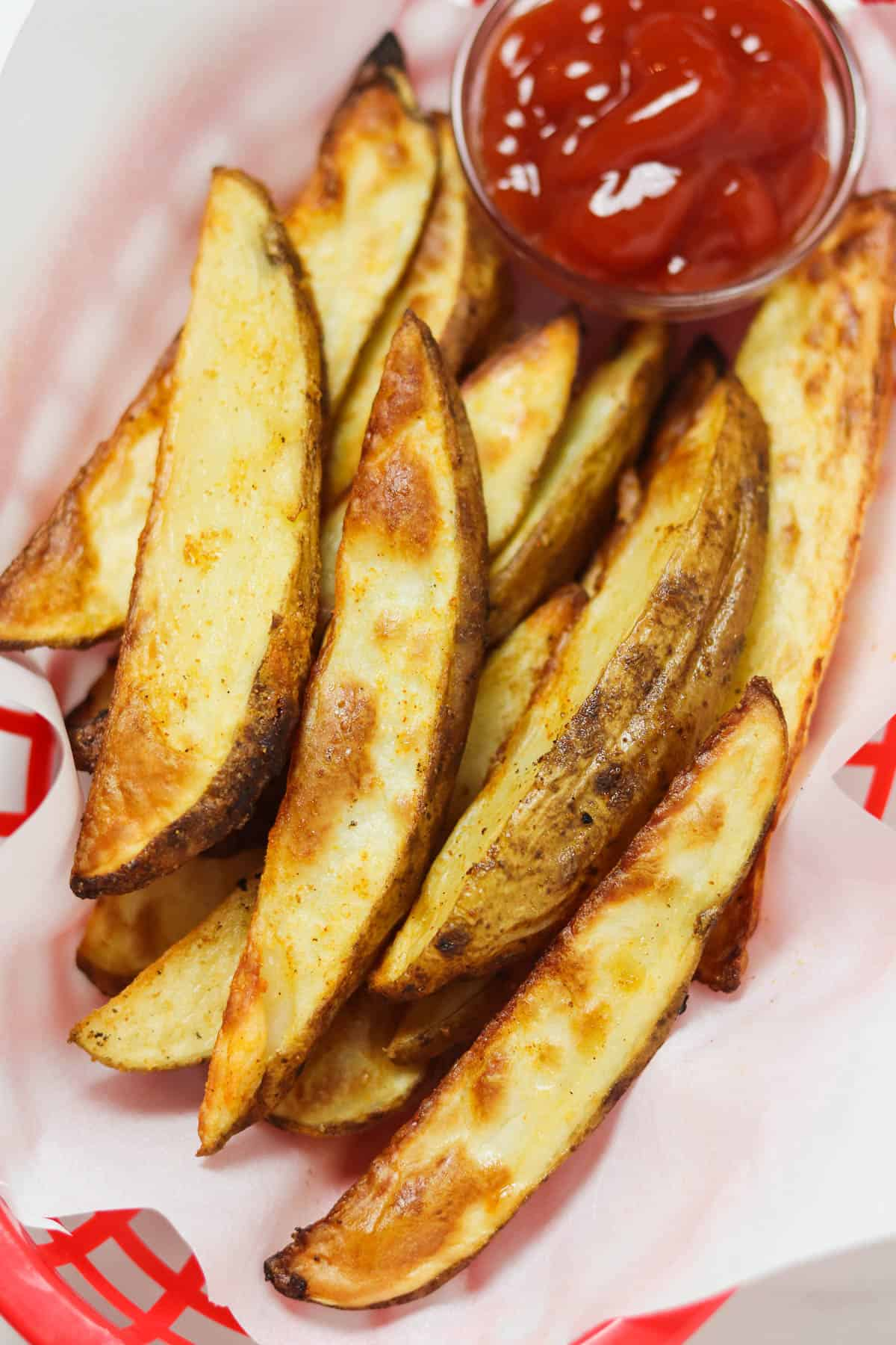 air fryer potato wedges in basket with ketchup