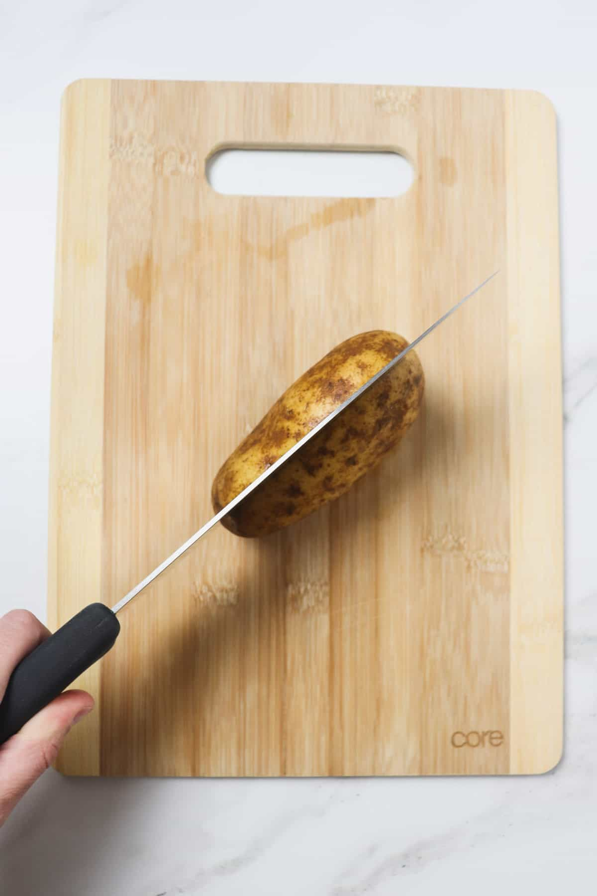 slicing a potato in half on a wood cutting board