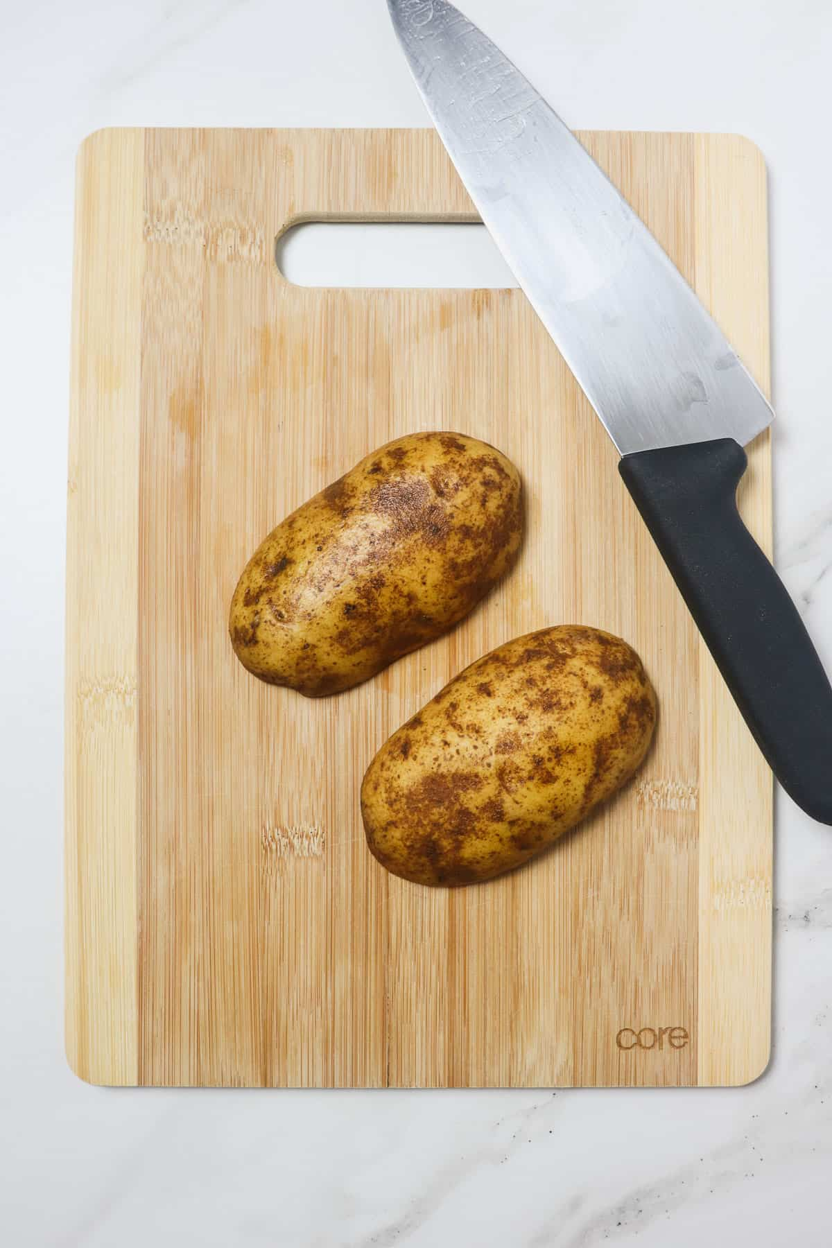 potato sliced in half on a wood cutting board
