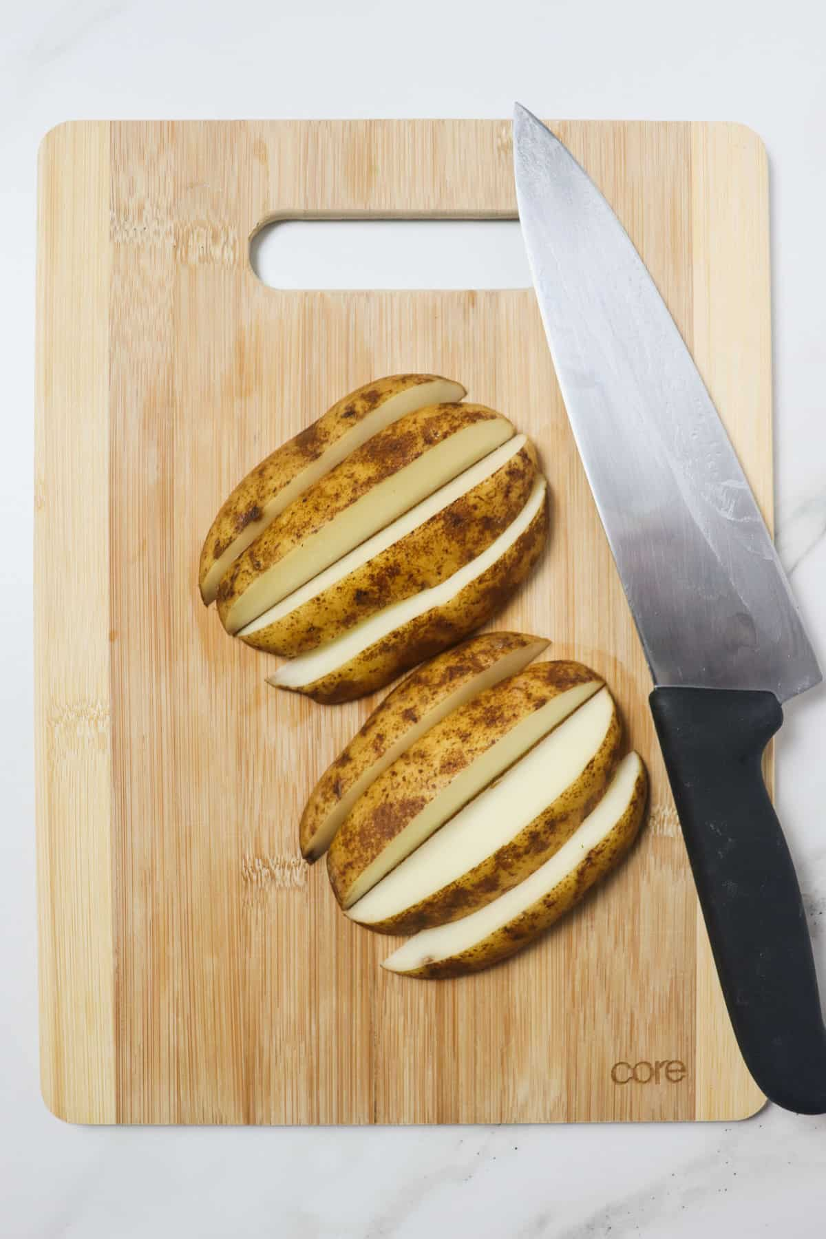cutting potatoes into wedges on a wood cutting board