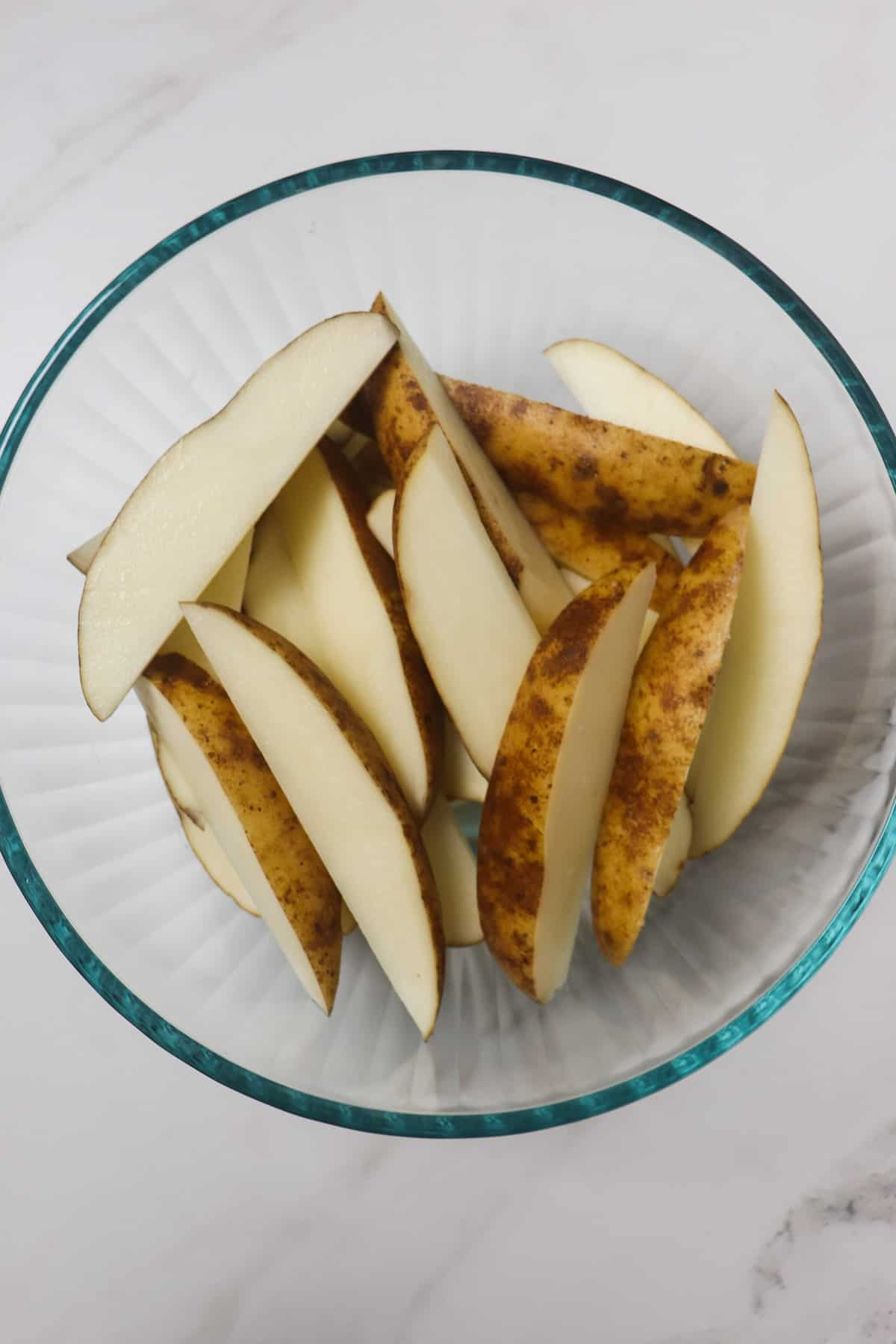 cut potato wedges in a glass bowl