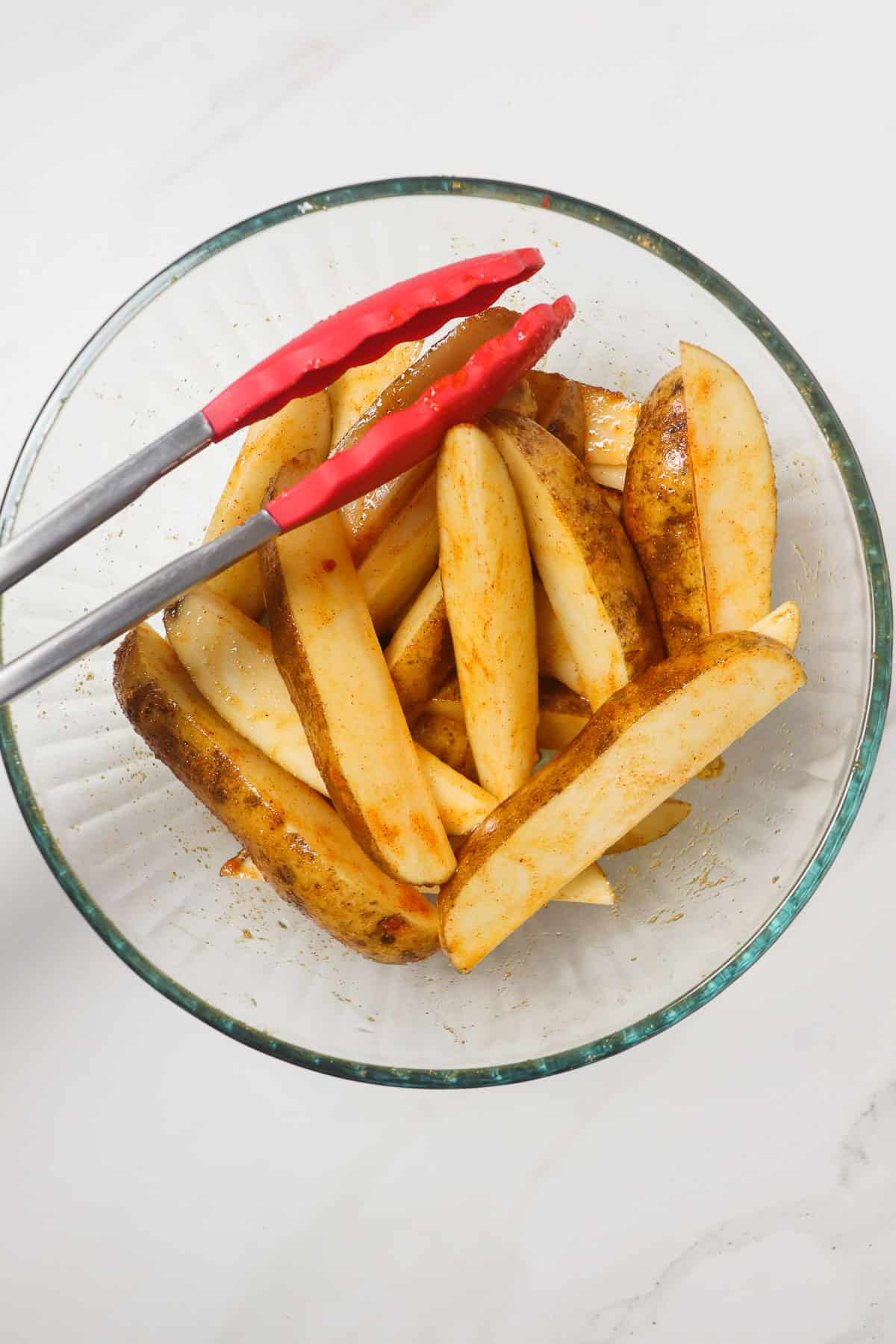 tossing potato wedges in oil and seasoning in a large glass bowl