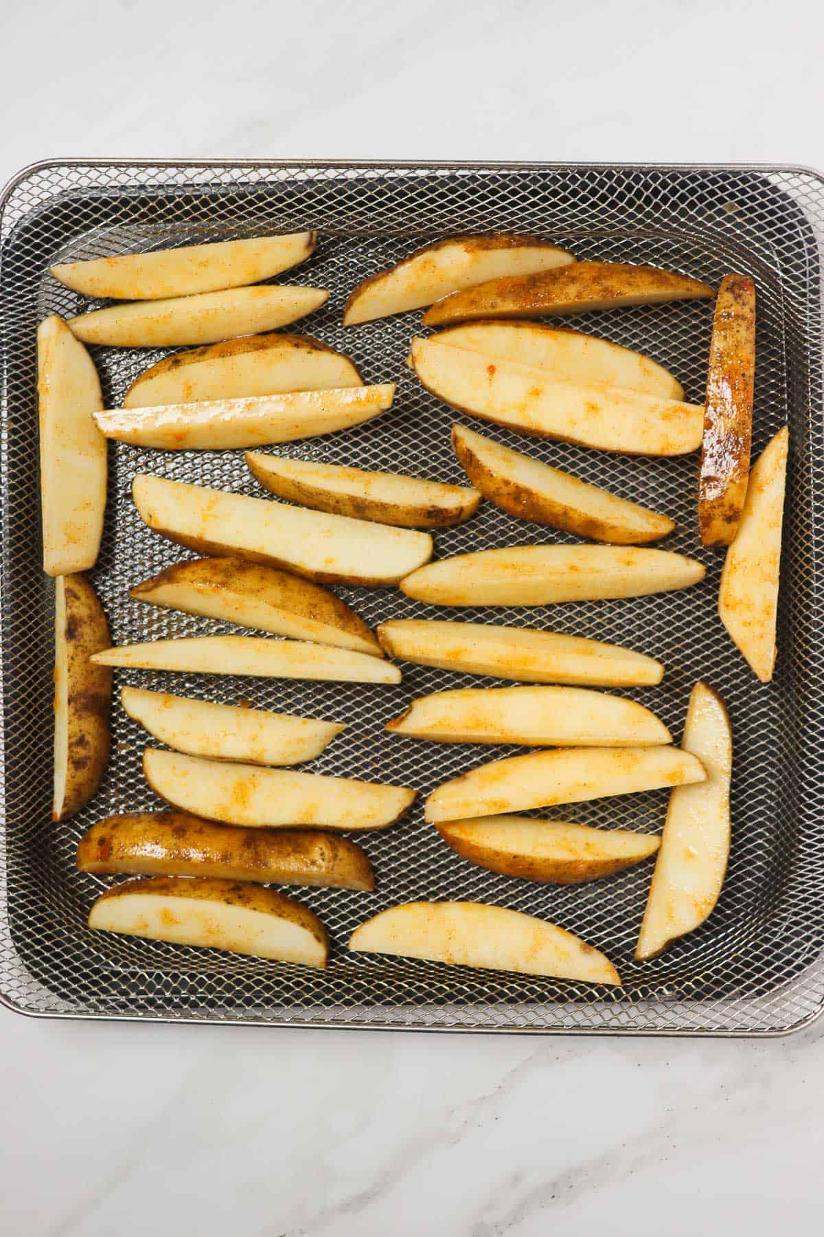 uncooked potato wedges loaded in air fryer basket