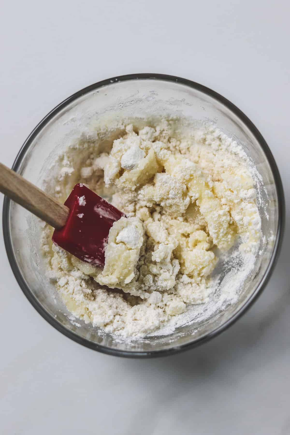 mixing flour with butter and sugar mixture in a small glass bowl