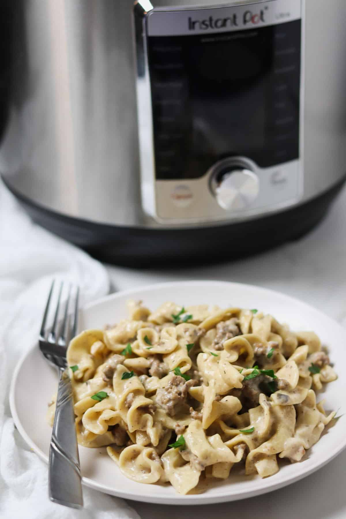 ground beef stroganoff on a white plate with fork with the instant pot in the background