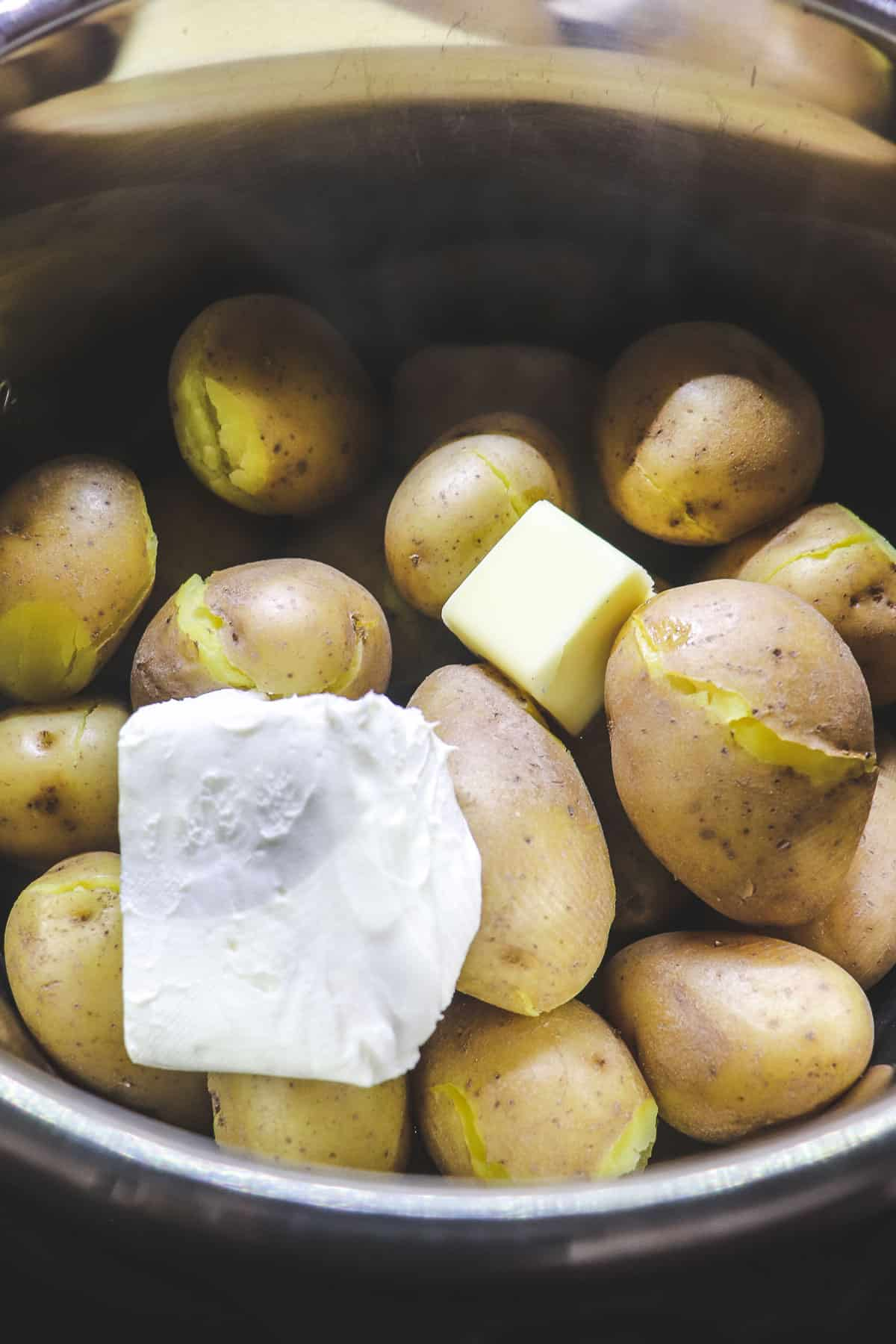adding cream cheese and butter to cooked potatoes in the instant pot