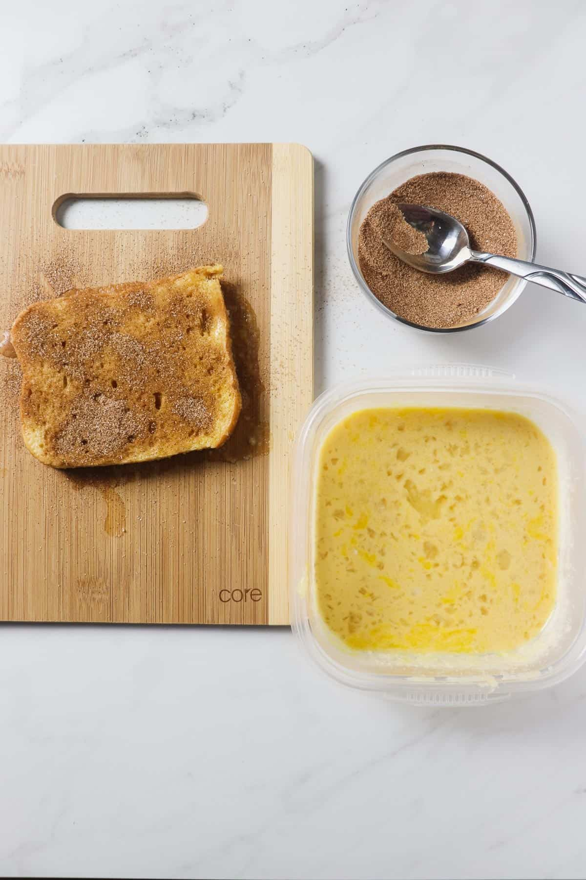 preparing french toast on a cutting board with an egg and milk mixture and cinnamon sugar mixture