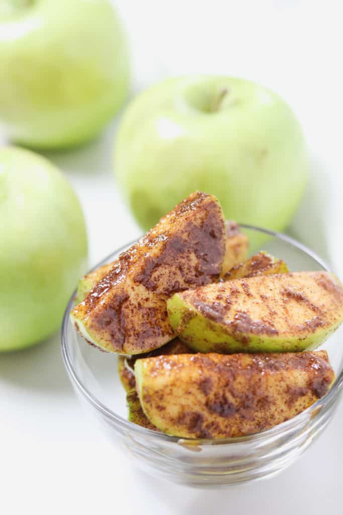 small glass bowl of cinnamon sugar apple slices with green apples in the background