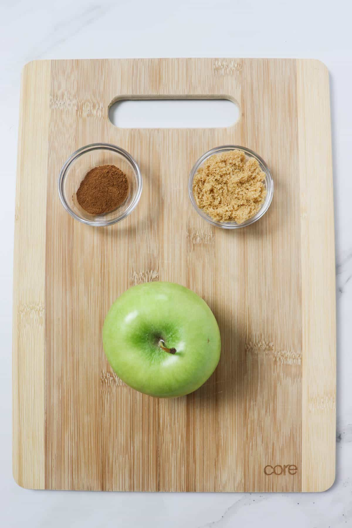 cinnamon, brown sugar, and granny smith apple on top of a wood cutting board