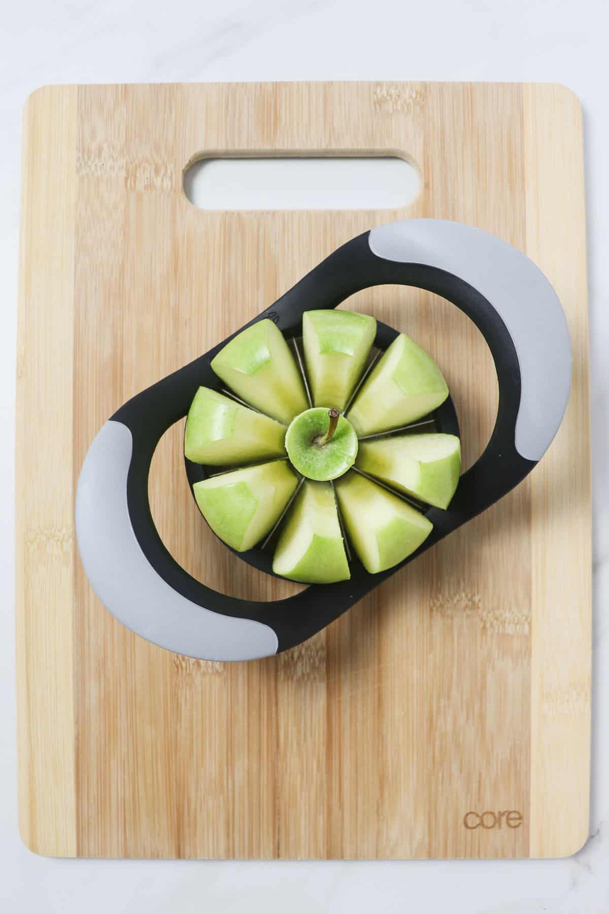 slicing an apple into wedges on top of a wood cutting board