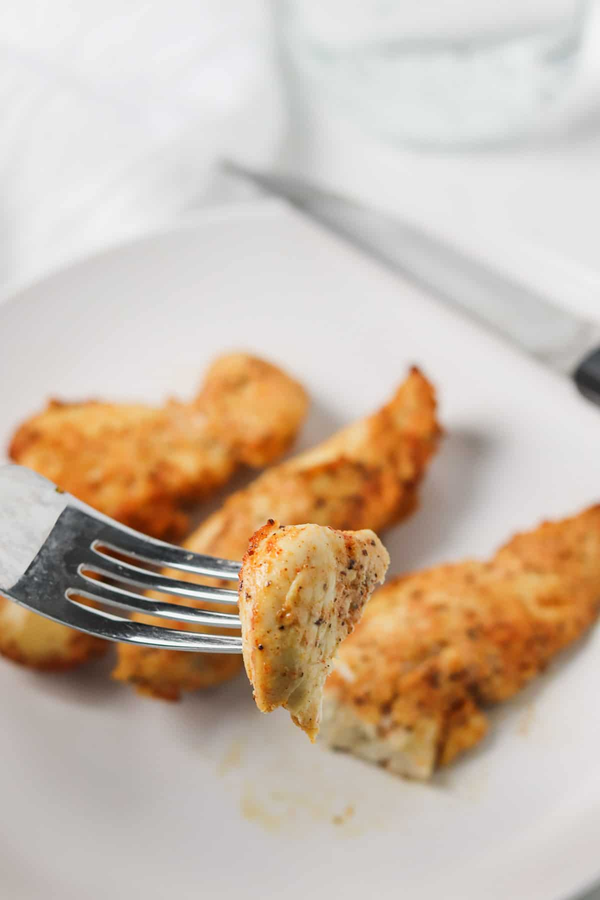 taking a bite of air fryer chicken tender with a fork
