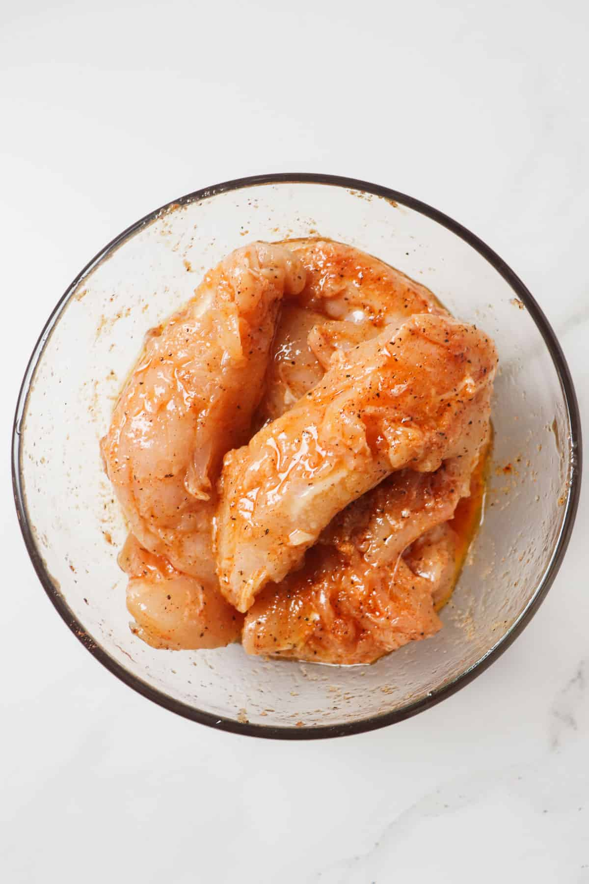 raw chicken tenders marinating in glass bowl