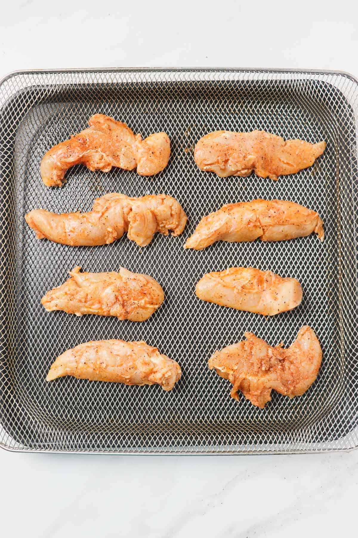 raw chicken tenders in air fryer basket