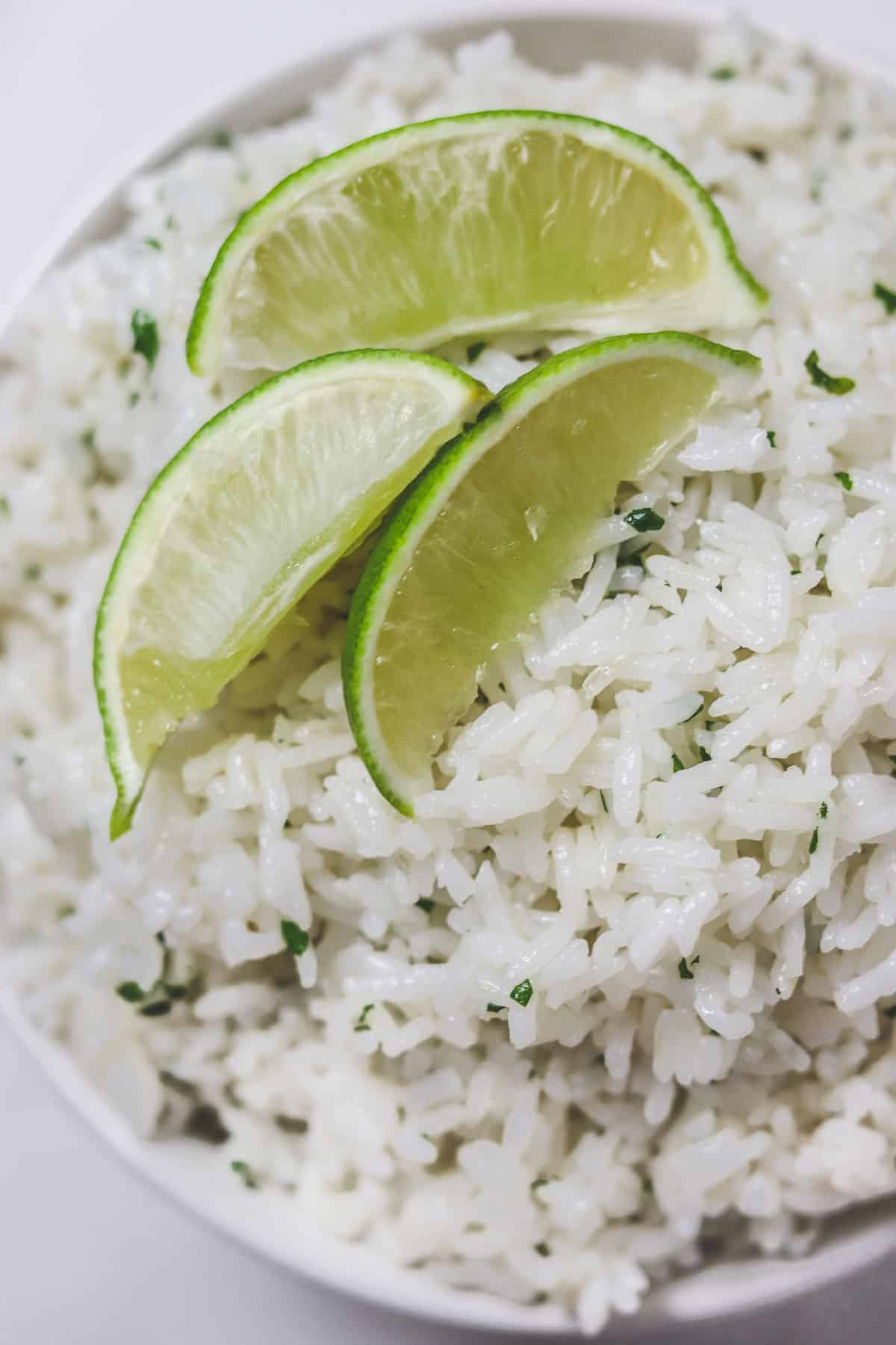bowl of cilantro lime rice with lime wedges on top