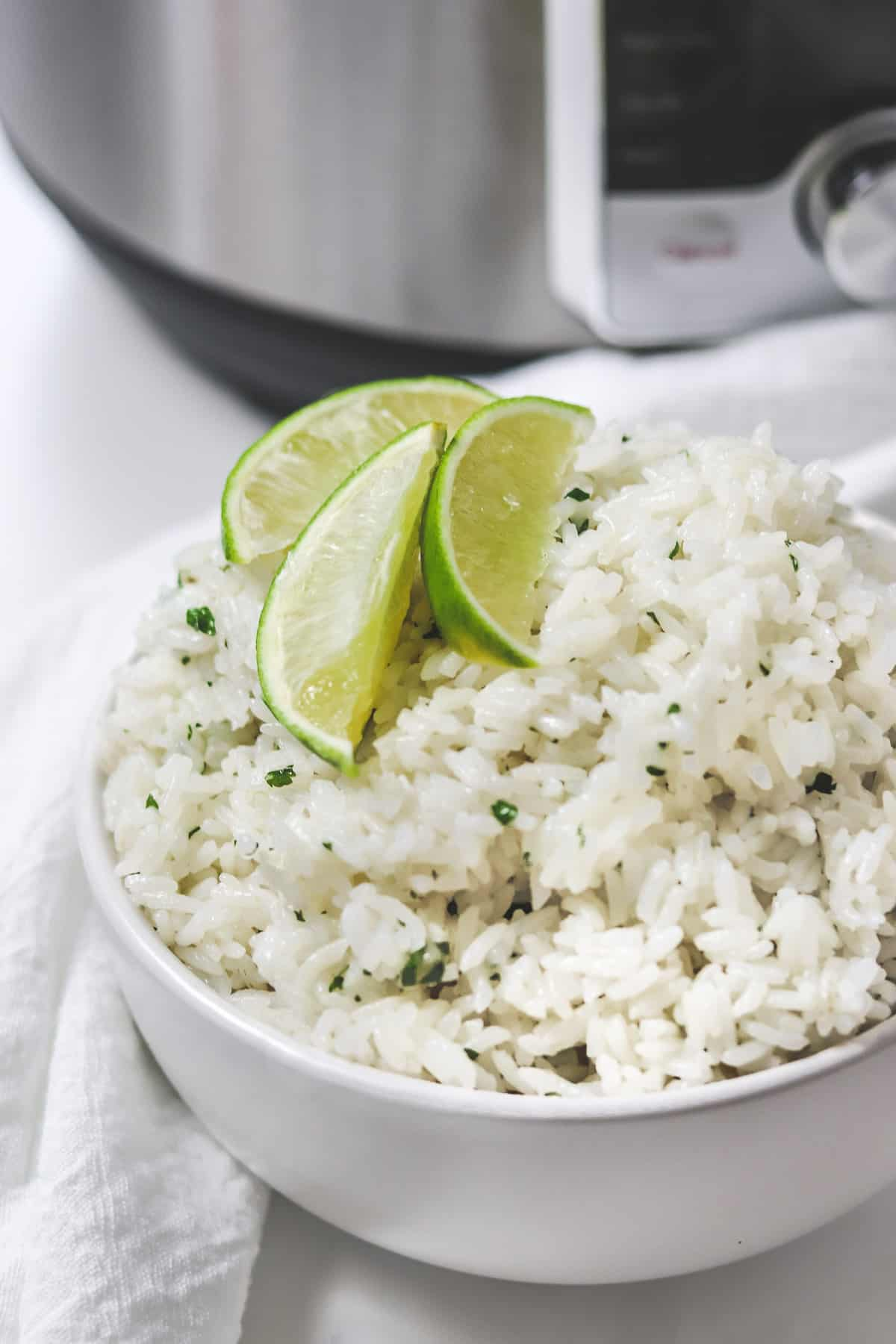 bowl of cilantro lime rice with lime wedges in front of instant pot