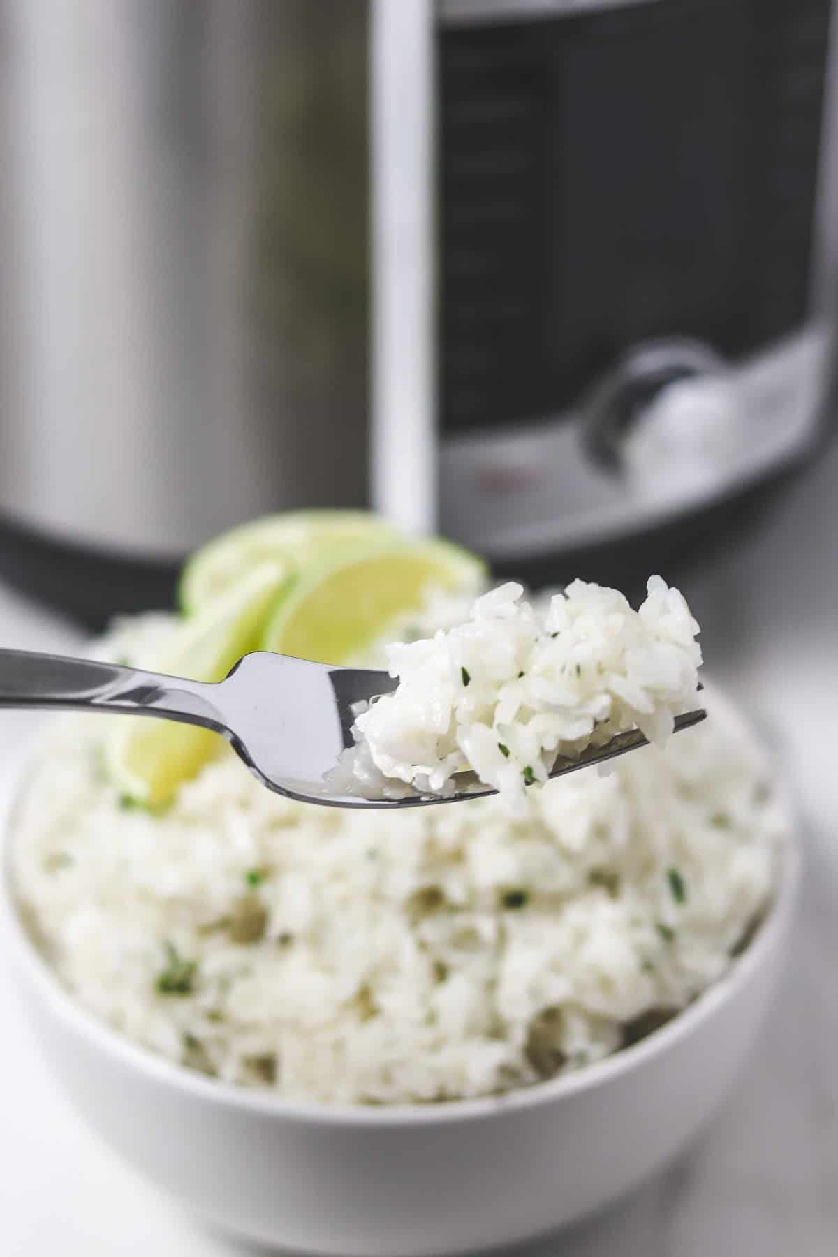 bite of cilantro lime rice on fork in front of bowl of rice and instant pot