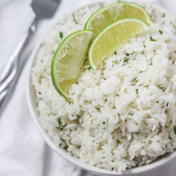 cilantro lime rice in bowl with lime wedges on top