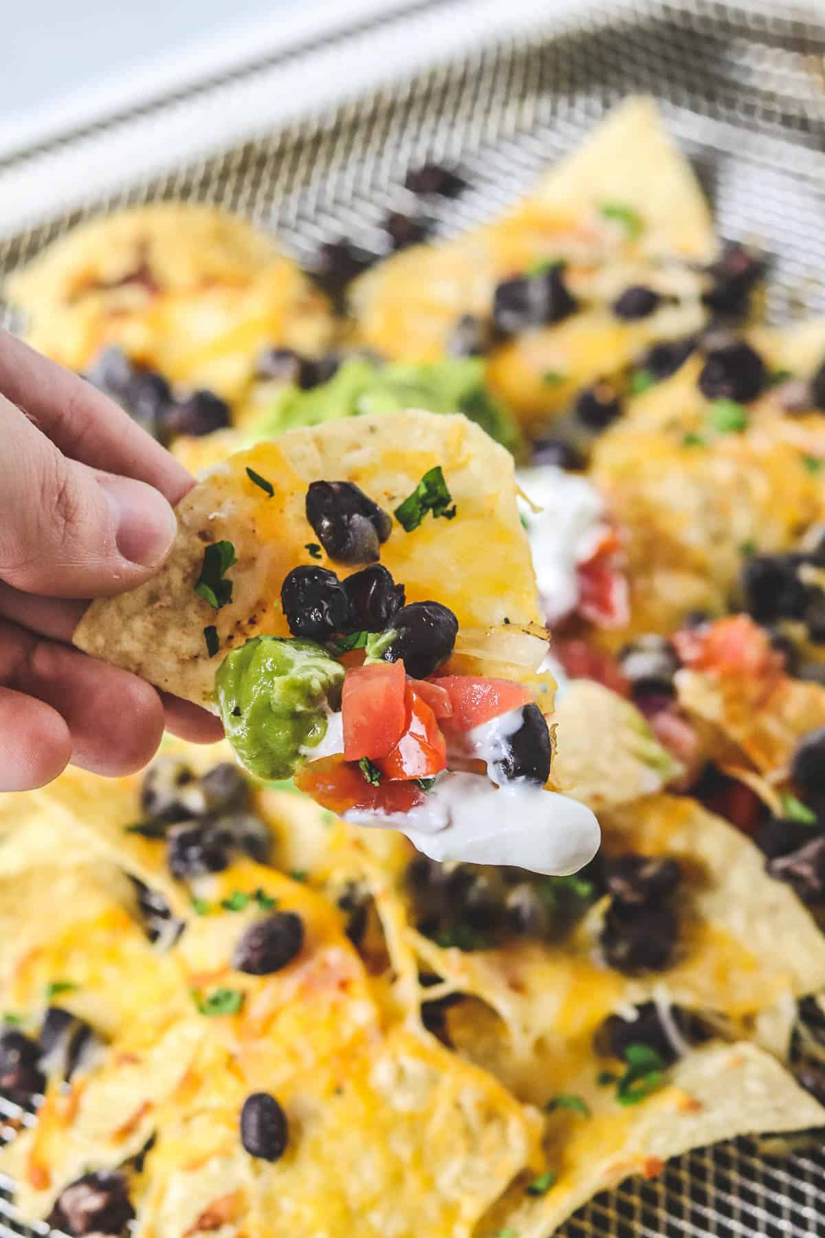 holding a chip of nachos with black beans, cheese, guacamole, sour cream, and pico de gallo