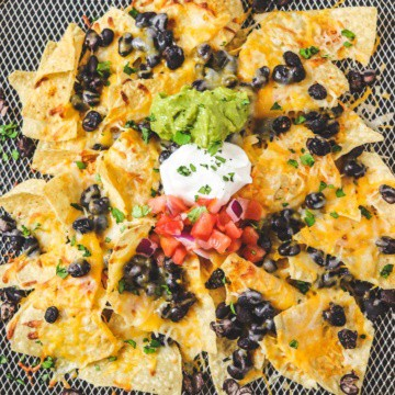 top down view of air fryer nachos in basket with toppings