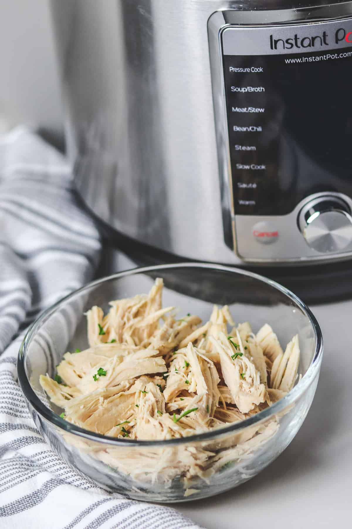 bowl of shredded chicken in front of the instant pot
